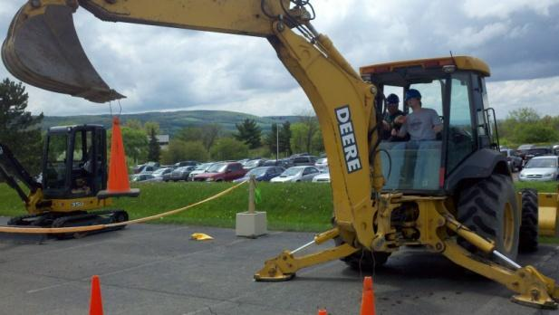 (Left) John Locklin shows a student the ropes on Economy Paving s backhoe at the 7 th Annual Central New York Careers in Construction at the Tompkins Cortland Community College on May 19, 2011.
