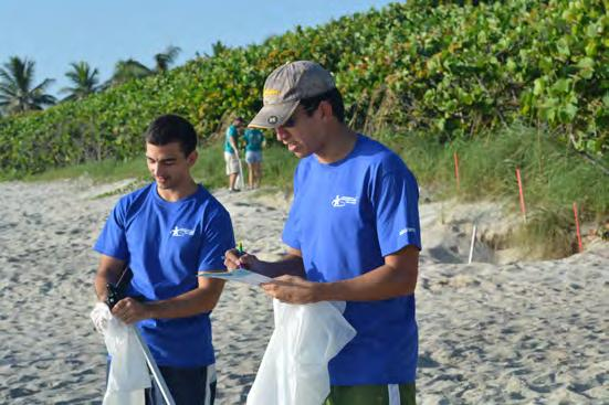 11 Javier Cué (left) and Winston Chico record data about the types and amounts of trash collected during the beach clean up event.