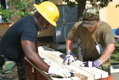 Jhon Mosquera (left) and Pfc. Ilija Marakovic - a Croatian soldier work at sanding the slats to be used on the benches at the playground.