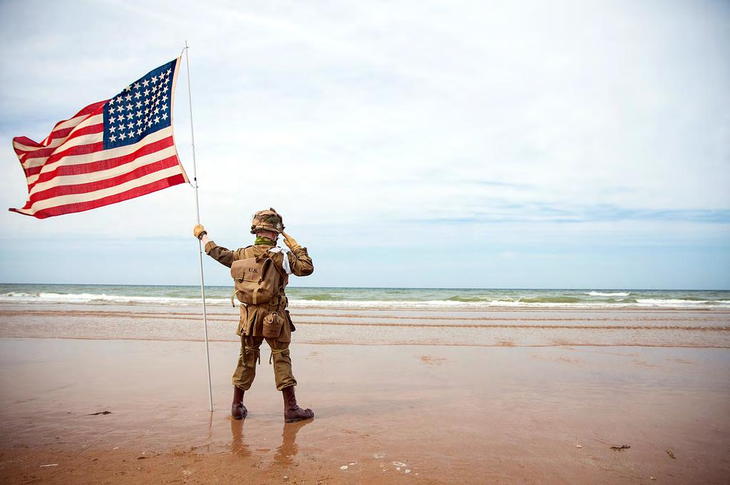 A French child, dressed as an American World War II Soldier stands tall, June, 0, while saluting the sands of Omaha Beach, France.