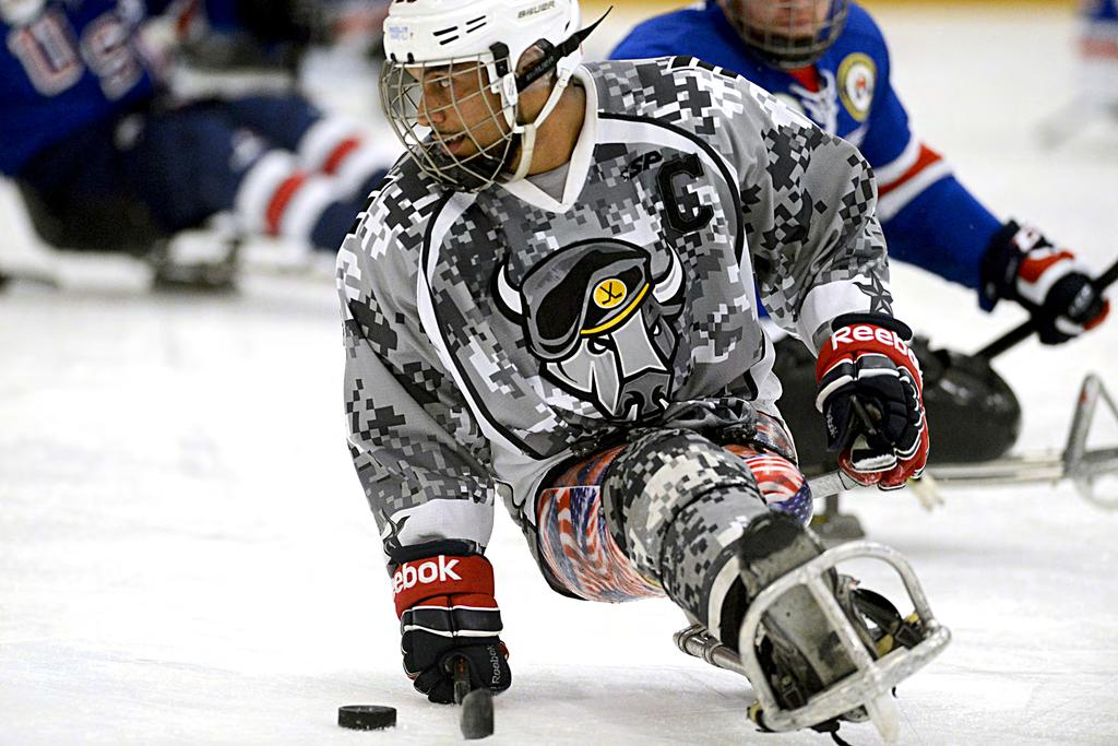 Army veteran Rico Roman of the San Antonio Rampage handles a puck during a sled hockey game with the USA Warriors in Rockville, Md., Sept., 0. Roman is a member of the gold medal U.S. National Sled Hockey Team in the 0 Paralympics in Sochi.