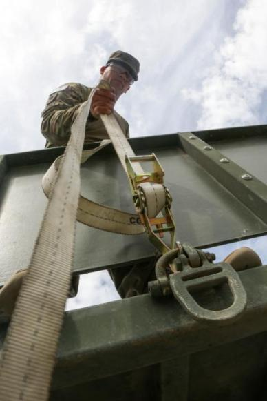 Division, prepares cargo straps on the back of a truck during retrograde operations at Forward Operation Base (FOB)