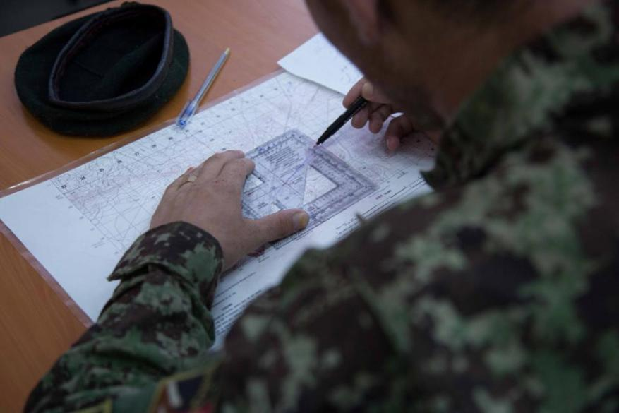 Afghan National Army (ANA) soldier plots coordinates during a call for fire training exercise at Forward Operating Base Gamberi, Laghman province, Afghanistan, May