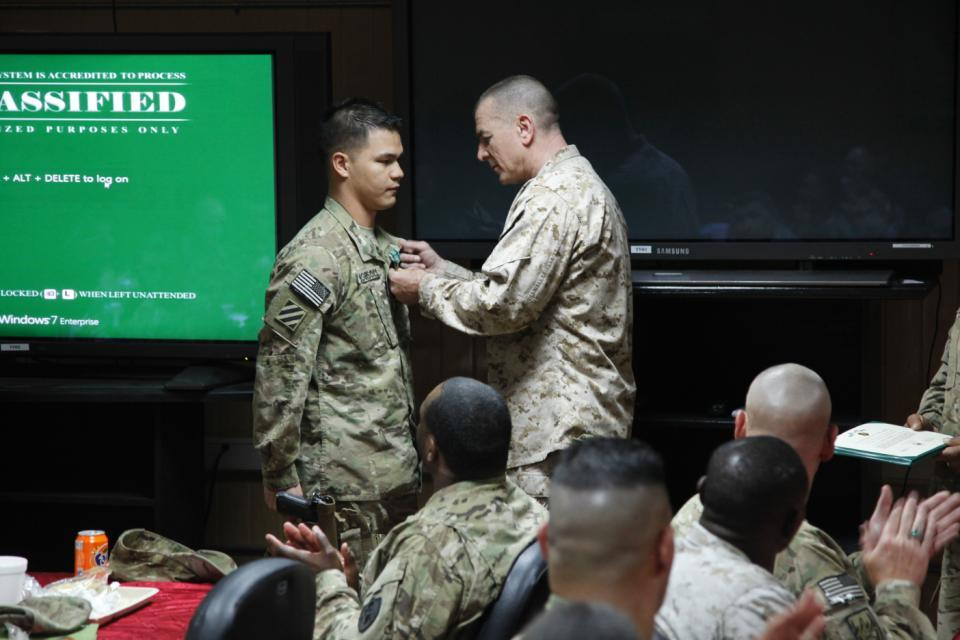 Sgt. Maj. Bryan B. Battaglia, Senior Enlisted Advisor to the Chairman of the Joint Chiefs, pins an Army Commendation Medal on Sgt.