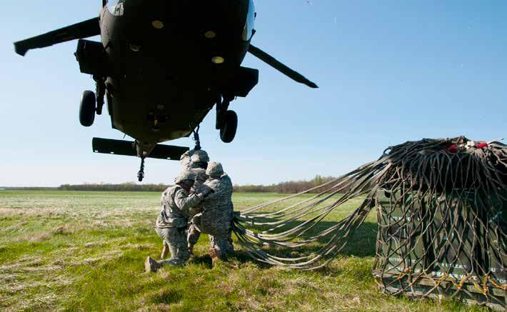 Soldiers from the 700th Brigade Support Battalion, Oklahoma Army National Guard, latch supplies onto a hovering UH- 60 Black Hawk helicopter during their annual training at the Sustainment Training
