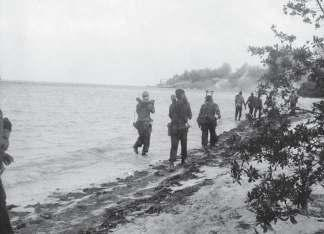 Photographed on April 19, Cuban troops carry mortar equipment along a beach; the SS Houston is seen still ablaze in the distance, which may place these men on the western shore of the Bay of Pigs,