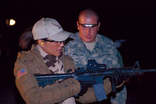 Jay Venturini LSA ANACONDA, Iraq Model Leann Tweeden prepares to fire an M-4 carbine as a range safety noncommissioned officer supervises
