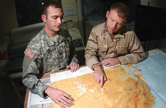 Photo by U.S. Air Force SrA Ricky Best Army CPT Eugene Hunt and Air Force Capt Charles Carter review an aeronautical chart used by 379 th Air Expeditionary Wing (AEW) aircrews.