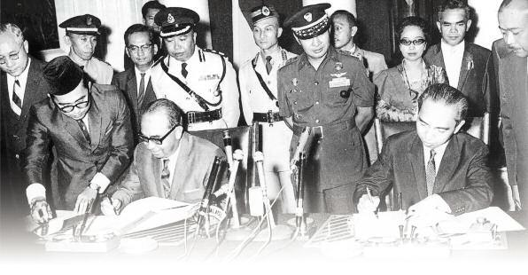 Tun Abdul Razak (left) with Dr Adam Malik (right) signing the peace treaty. Standing between them is Indonesian Army Chief, General Suharto.